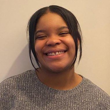 Aliyah Forde smiles extremely widely against a white background, she's wearing a grey jumper