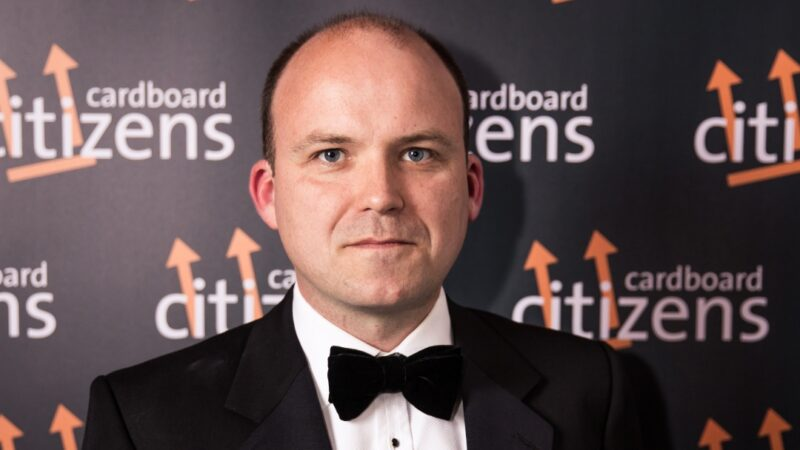 Rory Kinnear stands in front of a Cardboard Citizens banner