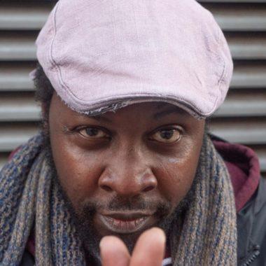 a close up of a man wearing a pink cap