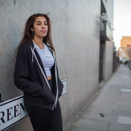 a woman leaning against a wall with an empty street behind her