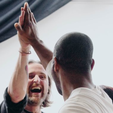 two men high fiving and smiling