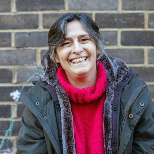 a woman wearing a red jumper and a coat, she is laughing