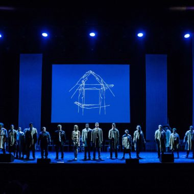 a long shot taken of a group of people standing on a stage taking a bow. The stage is lit with blue lighting.
