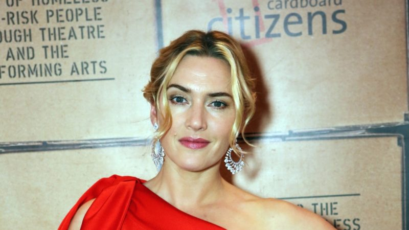 Kate Winslet with her hands on her hips wearing a red dress