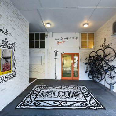 Entrance of a building showing a bike rack and a large sign painted on the floor saying Welcome