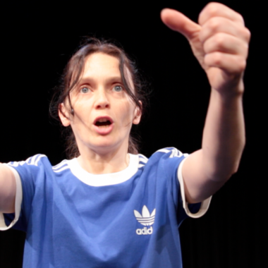 Eve Steele performing Life By The Throat against a black background - she wears a blue Adidas top and raises her two fists to the camera, as if driving
