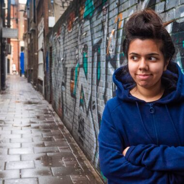 Anisah Chowdhury stands in an alleyway, wearing a blue hoody