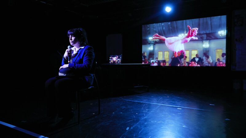 A production image from the Cardboard Citizens production Bystanders - Libby Liburd sits in front of a video screen