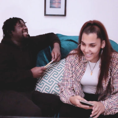 Terell And Beyonce from No Box No Label sit on a sofa and laugh