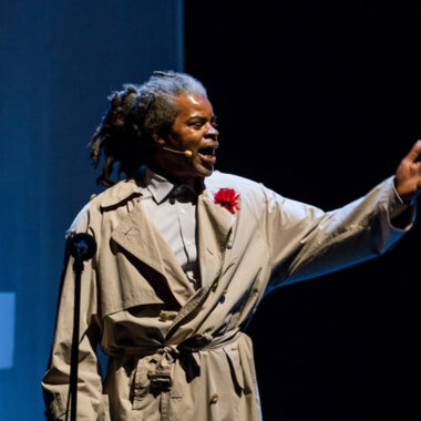 A Cardboard Citizens Member performs on stage at the Barbican - he's wearing a beige raincoat and a red flower in his lapel