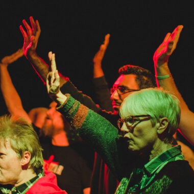 A group of people in a performance raise their hands in defiance